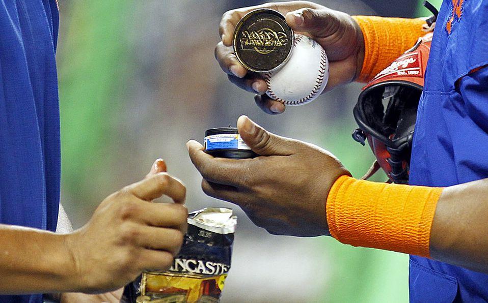 Peloteros sacan tabaco para mascar de su envase. Foto: AP
